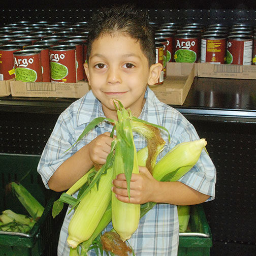 Milwaukee Christian Center Food Pantry Boy With Corn Photo